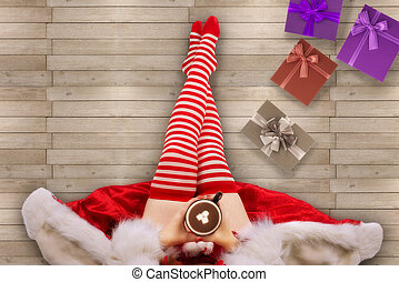 Girl wearing red and white socks, sits on a white wooden floor. Directly above. Cozy Christmas Holidays concept.