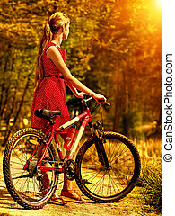 Girl wearing red dress rides bicycle in autumn park. - Girl ...