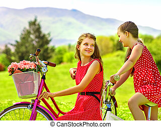 Girl wearing red polka dots dress rides bicycle into park...