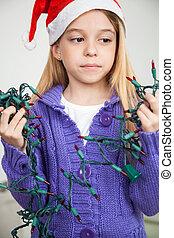 Girl Wearing Santa Hat Looking At Fairy Lights