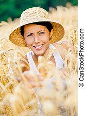 Girl wearing straw hat is in rye field