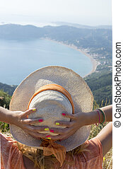 Girl wearing straw hat looking at the seaside from mountain viewpoint