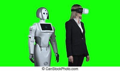 Girl wearing virtual reality glasses and a puts has hand to the side and the robot repeats after her. Green screen