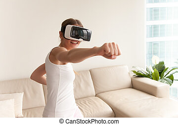 Girl wearing VR glasses playing game, boxing in virtual...