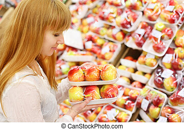 Girl wearing white shirt looks at packed apples in store; shallow depth of field