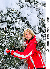 Girl wearing winter clothes shakes off from branches of trees.