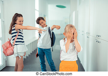 Girl wearing yellow skirt feeling stressed with rude classmates
