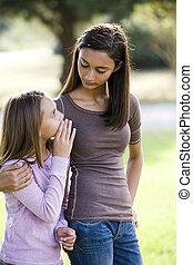 Girl whispering to her older teenage sister - Ten year old...