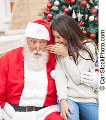 Girl Whispering Wish In Santa Claus's Ear - Girl whispering...