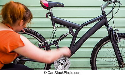 Girl wiping a bicycle with a cloth - A girl wipes a bicycle...