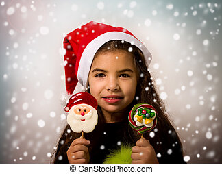 Girl Wit Candys - A little girl in a Santa Claus hat holds...