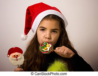 Girl Wit Candys - A little girl in a Santa Claus hat licks...