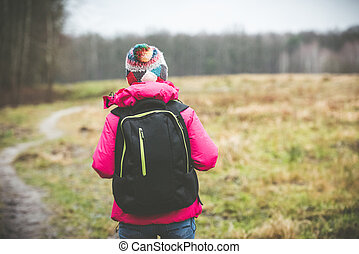 girl with a backpack going up the path