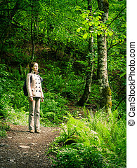 Girl with a backpack on the tourist trail in the spring forest