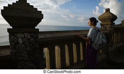 Girl with a backpack suited to a huge fence in front of a cliff and peering into the distance ocean shielding his eyes from the sun's light by hand.