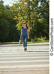 girl with a bag goes the way of pedestrian zebra - girl with...