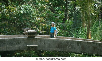 Girl with a bandage on his head and backpack goes through the old stone bridge in the tropical jungle. Tourist walking to exotic places in the resort. Incredibly beautiful nature on the island.