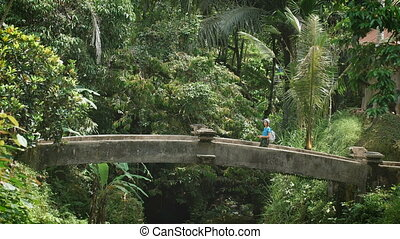 Girl with a bandage on his head and selfie stick in hand goes through the old stone bridge in the tropical jungle. Tourist walking to exotic places in the resort.