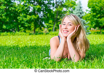 girl with a beautiful smile posing lying on the grass