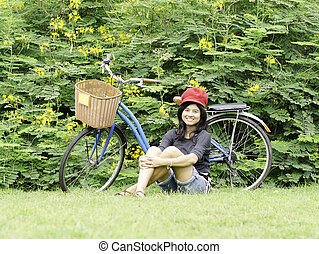 Girl with a bicycle rests on a grass