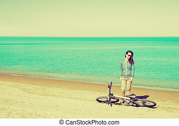 Girl with a bicycle standing on beach