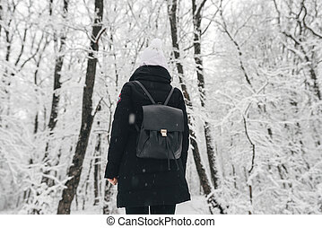 girl with a black backpack in a snowy forest