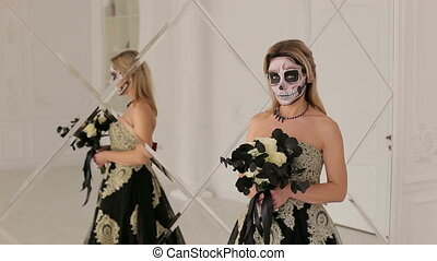 Girl with a black flowers and makeup for Halloween standing near mirror.