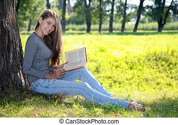Girl with a book in the park