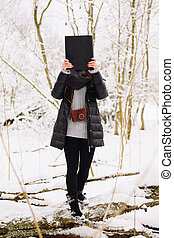 Girl with a book in the winter forest