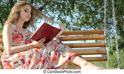 Girl with a book on a bench in the park