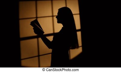 Girl with a book posing in profile. Dynamic change of focus