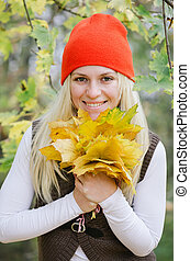 Girl with a bouquet of autumn leaves
