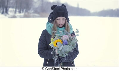 Girl with a bouquet of flowers on a frozen lake.Slow motion