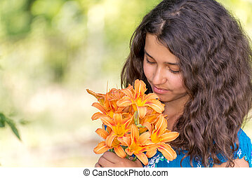 Girl with a bouquet of lilies in  park
