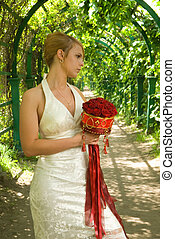 Girl with a bouquet of roses in green alley