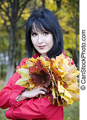Girl with a bouquet of yellow leaves