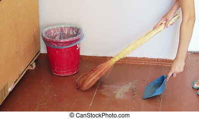 Girl with a broom sweeps debris on the floor and throws it in the trash dustpan.