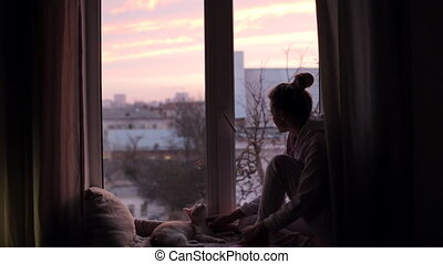 Girl with a cat sits on a windowsill in the early morning