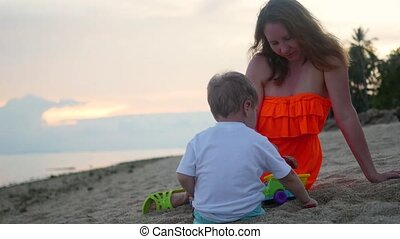 Girl with a child plays with sand on the beach at sunset time