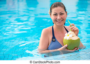 girl with a coconut in the pool resting