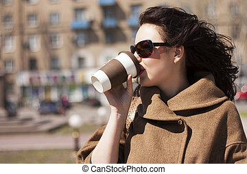 Girl with a coffee on the street.