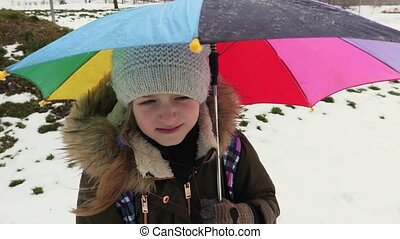 Girl with a colorful umbrella in park