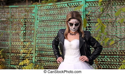 Girl with a creepy make-up for Halloween on the background of an old rusty fence