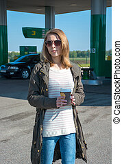 Girl with a cup of coffee at a gas station