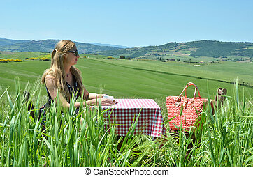 Girl with a cup of coffee at the table on theTuscan field. Italy