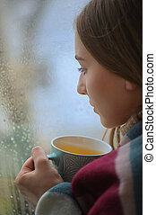 Girl With A Cup Of Hot Drink In Front Of A Window
