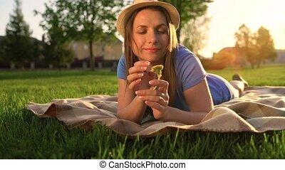 Girl with a dandelion in her hands relaxes lying down on a blanket in the park at sunset