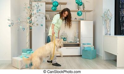 girl with a dog is playing with a hoop in room with Christmas decorations