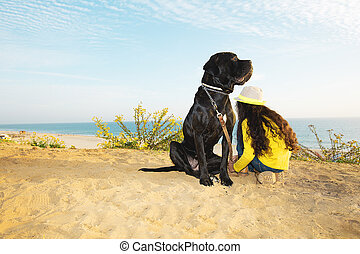 Girl  with a dog sitting on the beach