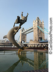 Girl with a dolphin statue near Tower Bridge UK